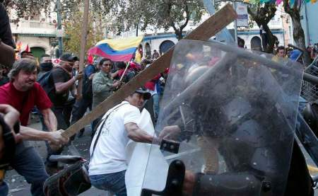 Demonstrators clash with the police during a march in Quito